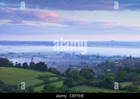 The town of Glastonbury and the Somerset Levels, shrouded in mist, from Glastonbury Tor, in pre-dawn light. - Stock Photo