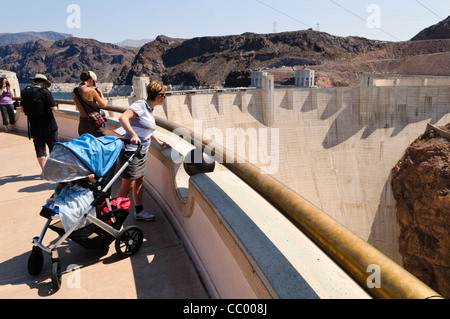 HOOVER DAM, Nevada - Tourists overlook the Hoover Dam's massive concrete wall from a viewing platform at the top - Stock Photo