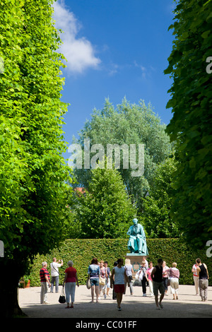 People visiting the H. C. Andersen statue in Rosenborg Castle Gardens - Stock Photo