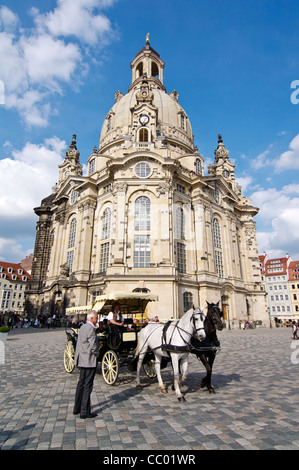 Carriage and horses on the cobblestone square in front of the historic Frauenkirche dome in Dresden, Germany - Stock Photo