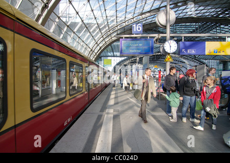 Busy passengers under the curved glass roof of the Hauptbahnhof train station in Berlin, Germany - Stock Photo