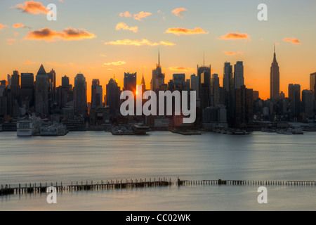 The rising sun shines through the buildings of the mid-town Manhattan skyline at sunrise as viewed New Jersey. - Stock Photo