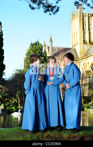 Boy choristers from the Wells Cathedral Choir in Somerset UK take a break from rehearsals by 'The Wells' pond after - Stock Photo