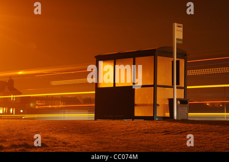 Bus Stop at night with light trail from a bus - Stock Photo