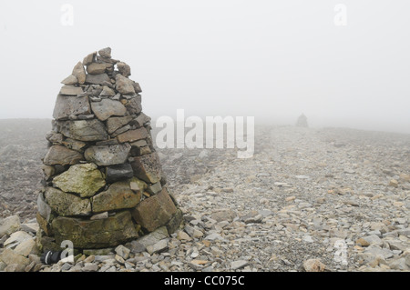 This image shows two cairns on top of Ben Nevis, Scotland, along a path that allows visitors to find there way to - Stock Photo