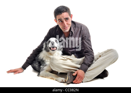 portrait of purebred border collie and smiling young man in front of white background - Stock Photo