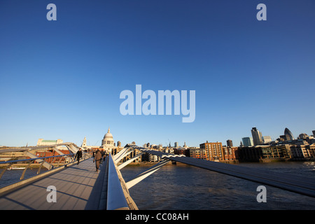 people crossing the millenium footbridge over the river thames in early morning city of London England UK United - Stock Photo