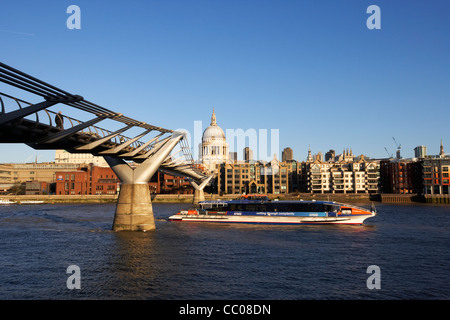 the millenium footbridge over the river thames and thames clipper riverboat in early morning city of London England - Stock Photo