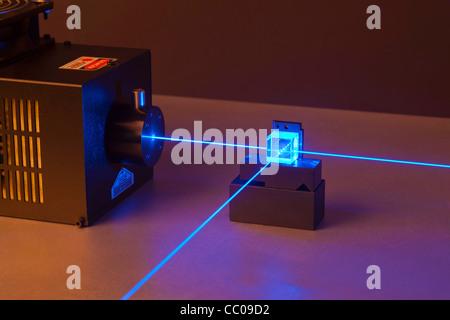 argon ion laser beam passing through a beam splitter - Stock Photo