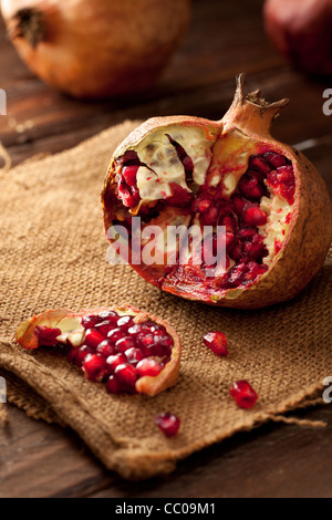 Pomegranate with Seeds on Jute and Wood - Stock Photo