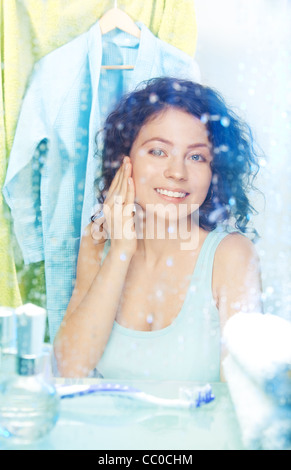 Young beautiful woman washing face and smiling in the morning - Stock Photo