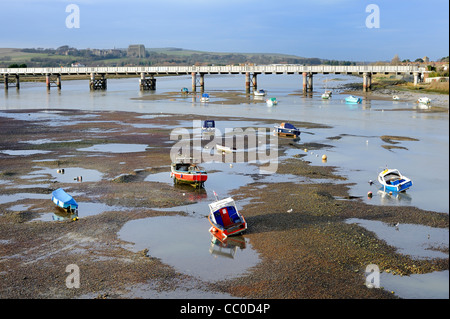 Boats stranded at low tide on river Adur with railway bridge and Lancing college in Background - Stock Photo