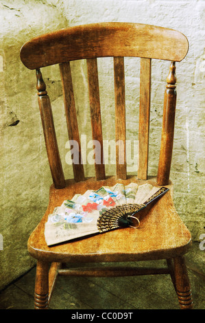 Old fashioned hand fan over an old wooden chair - Stock Photo