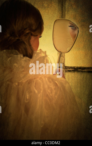 Rear view of a woman looking into a mirror - Stock Photo