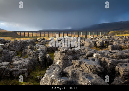 Snow Showers Limestone Pavement rocks at the Ribblehead Viaduct across the River Ribble at Ribblehead , in North - Stock Photo