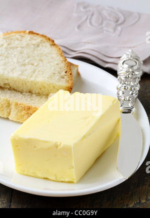 fresh yellow butter on a wooden stand, organic produce - Stock Photo