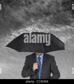 Businessman sheltering from the rain - Stock Photo