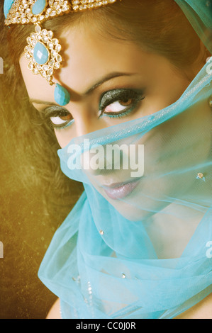 Serious Indian woman covering her face with blue veil looking away - Stock Photo