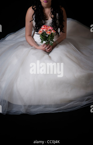 Bride in white wedding dress holding flowers bouquet - Stock Photo