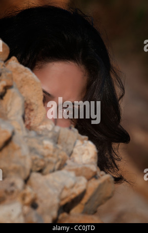Serious young woman hiding behind rocks - Stock Photo