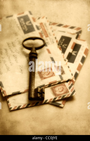 Rusted key over a collection of old letters - Stock Photo