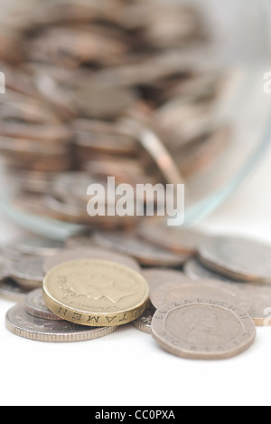Spilled Coins from Glass Jar, focus on £1 coin. Sterling. - Stock Photo