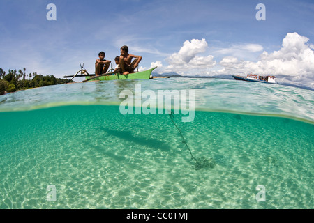 Boys fishing from an outrigger in Indonesia. Bangka Island, North Sulawesi, Indonesia, Pacific Ocean. - Stock Photo
