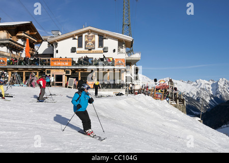 The Taps Coyotes and Krazy Kanguruh apres ski bars with skiers skiing on snow slopes in Austrian Alps in St Anton - Stock Photo