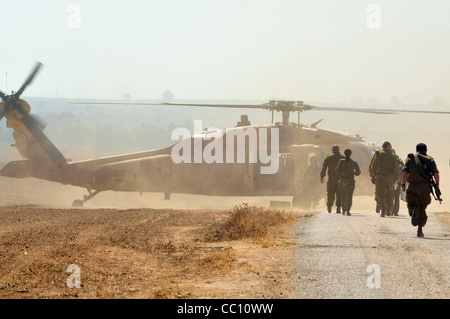 An Israeli military Sikorsky UH-60 Black Hawk during ascending and landing on land. - Stock Photo
