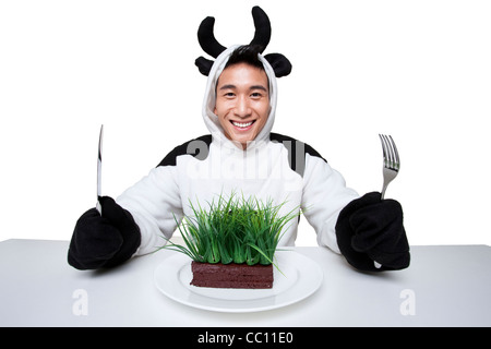 Man in a cow costumes with a serving of grass on his plate
