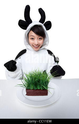 Woman in a cow costumes with a serving of grass on her plate