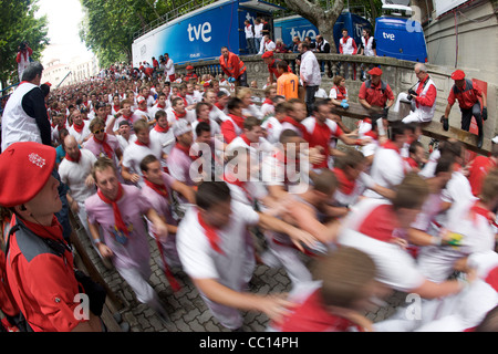 Crowds running in the encierro (bull run) during the festival of San Fermin (aka the running of the bulls) in Pamplona, - Stock Photo