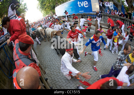 Crowds running with bulls during the annual festival of San Fermin (aka the running of the bulls) in Pamplona, Spain. - Stock Photo