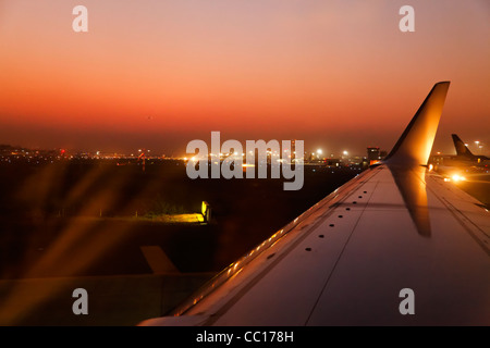 Horizontal landscape mumbai airport at twilight when a one plane taxi another one is landing. Glowing sunset colors - Stock Photo