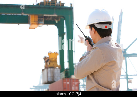 shipping industry worker directing cranes with his walkie-talkie - Stock Photo