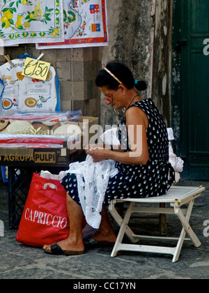 A lacemaker sits next to her stall on the street in Sorrento making lace. - Stock Photo