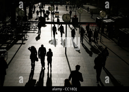 Shadows and silhouettes of pedestrians walking through Reuters Plaza, Canary Wharf, London, UK - Stock Photo
