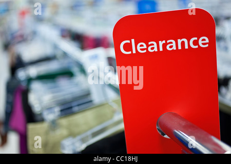 A red sale clearance sign on rail of clothes in a shop - Stock Photo