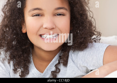 Studio shot of a beautiful young mixed race interracial African American girl child smiling - Stock Photo