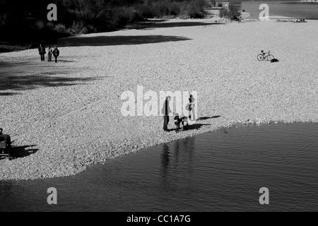 Black and white upper view of people gathering and walk along the banks of the Isar River in Munich, Germany. - Stock Photo