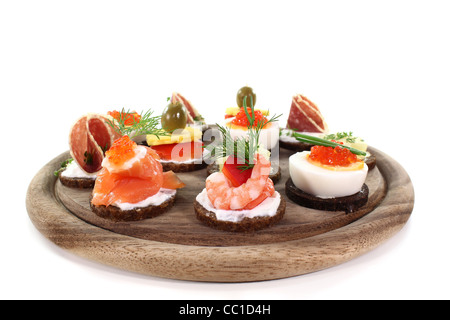 different canapés on a wooden board on a white background - Stock Photo