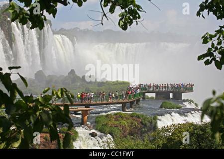 Tourists on walkway at the Iguazu Falls / Iguassu Falls / Iguaçu Falls on the border of Brazil and Argentina - Stock Photo