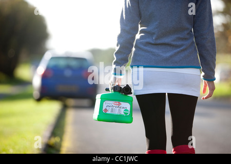A young woman walks to her car with a petrol can of fuel after running out of petrol at the side of the road. - Stock Photo