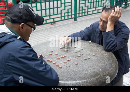 chinese men playing chinese chess at an outdoor municipal park table in hong kong hksar china asia - Stock Photo
