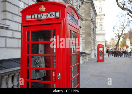 red telephone call boxes on the pavement in whitehall London England UK United kingdom - Stock Photo