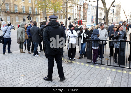 metropolitan police officer stands guard watching tourists outside the gates of downing street at whitehall London - Stock Photo