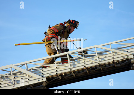 A firefighter climing over to a roof on a ladder fire truck - Stock Photo