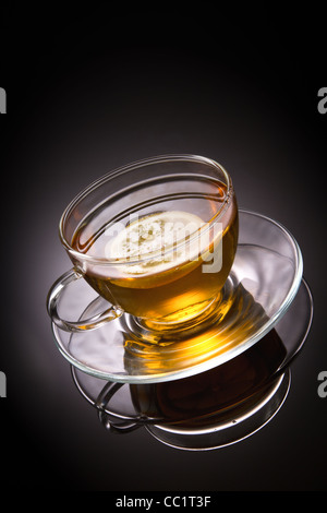 tea with lemon in glass cup on grey background - Stock Photo