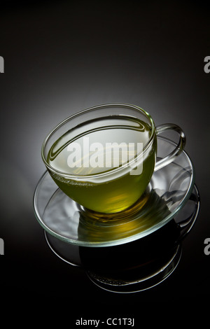Green tea in glass cup on grey background - Stock Photo