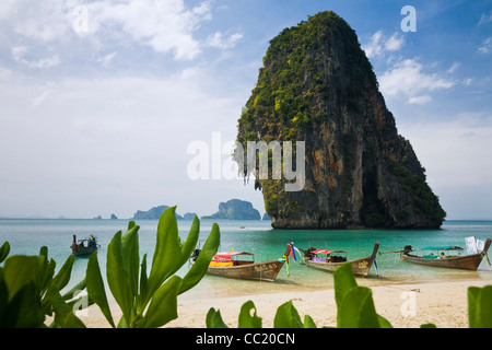 Longtail boats at Phra Nang Beach (Hat Phra Nang) with Happy Island in the background. Railay, Krabi, Thailand - Stock Photo